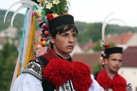 VLCNOV, CZECH REPUBLIC - MAY 26, 2013: Young man dressed in traditional Moravian folk costume perform the Recruit during the Ride of the Kings folklore festival in Vlcnov, South Moravia, Czech Republic.