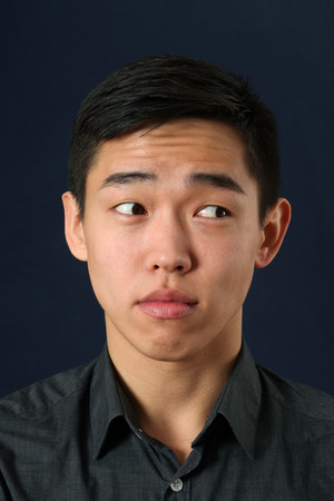 sidelong: Young Asian man looking sideways