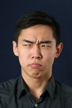 sidelong: Young Asian man making face and looking sideways Stock Photo