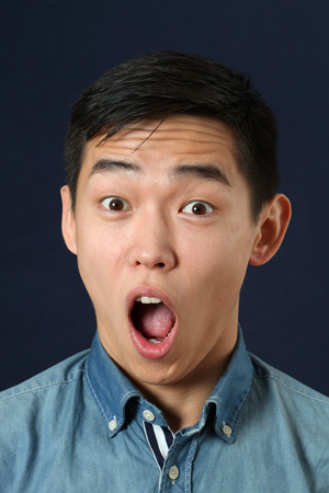 astonishment: Astonished young Asian man looking at camera with opened mouth