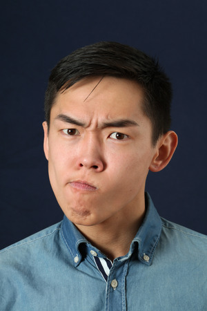 displeased: Displeased young Asian man making face and looking at camera