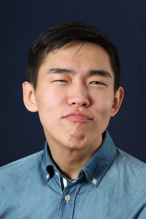pleased: Pleased young Asian man making face and looking at camera