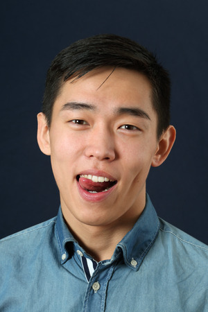 pleased: Pleased young Asian man showing his tongue and looking at camera