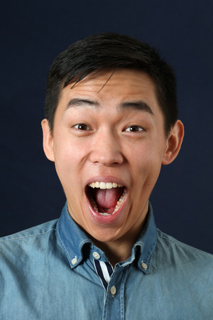 happy asian man: Surprised young Asian man crying and looking at camera Stock Photo