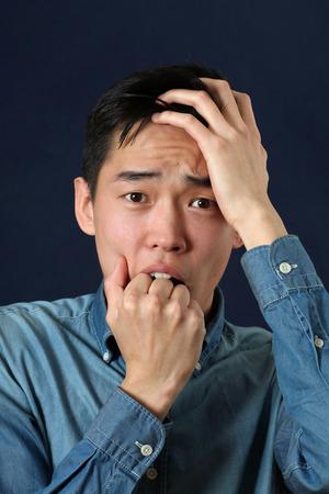 gestos de la cara: Hombre asi�tico joven decepcionante que mira la c�mara