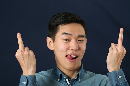 Funny young Asian man giving the finger signs with two hands photo
