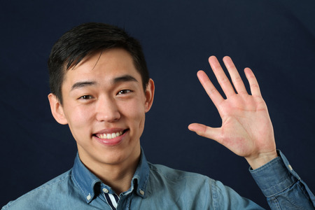 human palm: Smiling young Asian man waving his palm and looking at camera