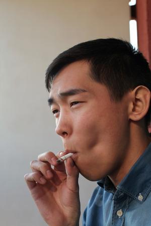 hombre fumando: Hombre asi�tico joven hermoso que fuma un cigarrillo