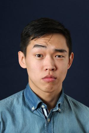 Serious young Asian man looking at camera photo