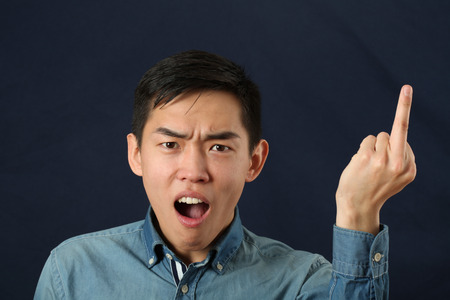 giving the finger: Angry young Asian man giving the middle finger sign and looking at camera Stock Photo