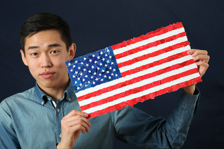 english ethnicity: Young Asian student showing US national flag and looking at camera