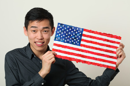 chinese american ethnicity: Young Asian student showing US national flag and looking at camera