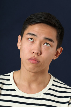 making face: Funny young Asian man making face and rolling eyes up Stock Photo