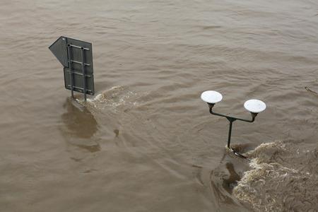 submerge: PRAGUE, CZECH REPUBLIC - JUNE 3, 2013: Street lamppost partially flooded by the swollen Vltava River in Prague, Czech Republic.