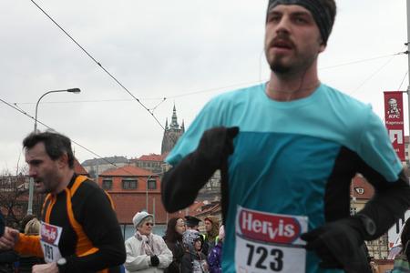 PRAGUE, CZECH REPUBLIC - APRIL 6, 2013: Athletes run in front of Prague Castle with St Vitus Cathedral during the Prague international marathon in Prague, Czech Republic. Editorial