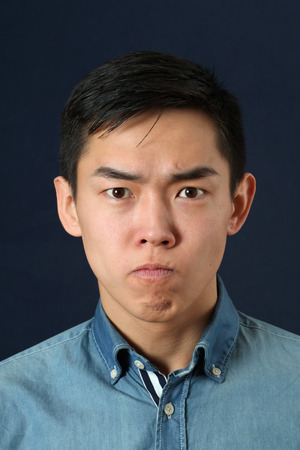 displeased: Displeased young Asian man looking at camera