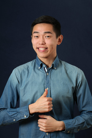 hombres jovenes: Sonriente hombre asi�tico joven que da los pulgares para arriba signo y mirando a c�mara
