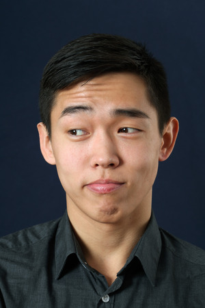 sidelong: Young Asian man rising eyebrows and looking sideways