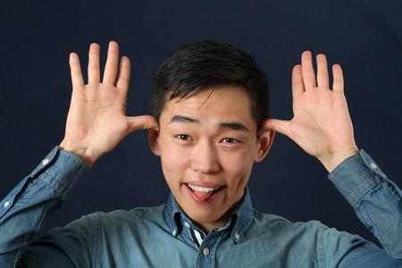 Funny young Asian man making face and looking at camera photo