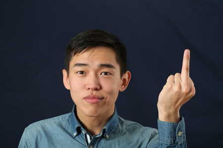 fuck: Young Asian man giving the middle finger sign and looking at camera
