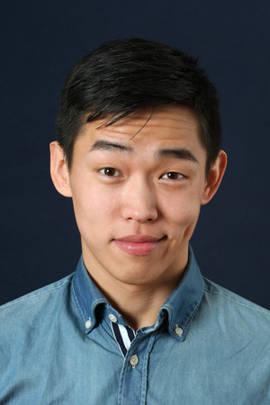 pleased: Pleased young Asian man looking at camera