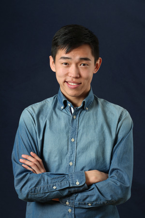 smirking: Smirking young Asian man with crossed hands looking at camera