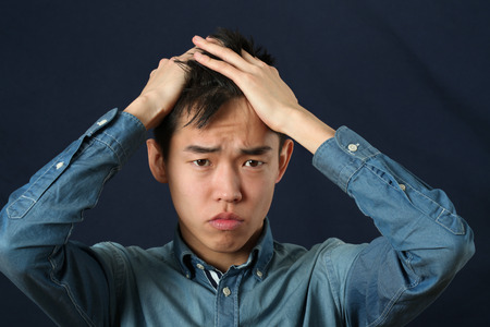 making face: Disappointed young Asian man making face and looking at camera