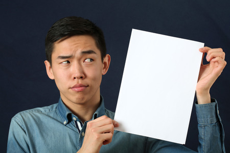 suspect: Funny young Asian man showing white copy space page and looking sideways