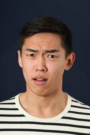 disgusted: Disgusted young Asian man looking at camera Stock Photo