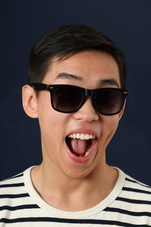 dark face: Laughing young Asian man in sunglasses Stock Photo