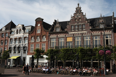 north holland: HAARLEM, NETHERLANDS - AUGUST 9, 2012: People sit in a cafe in front of the traditional Dutch houses on the Grote Markt in Haarlem, North Holland, Netherlands. Editorial