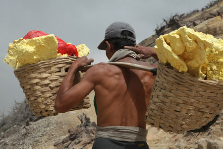 KAWAH IJEN, INDONESIA - AUGUST 8, 2011: Miner carries baskets with sulphur in the fumes of toxic volcanic gas from the sulphur mines in the crater of the active volcano of Kawah Ijen, East Java, Indonesia.