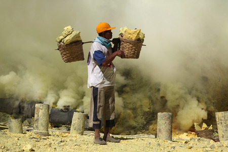 KAWAH IJEN, INDONESIA - AUGUST 8, 2011: Miner carries baskets with sulphur in the fumes of toxic volcanic gas at the sulphur mines in the crater of the active volcano of Kawah Ijen, East Java, Indonesia.