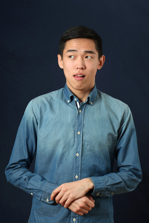 Young Asian man making face and looking sideways Stock Photo