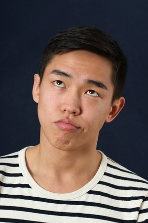 rolling up: Funny young Asian man making face and rolling eyes up Stock Photo