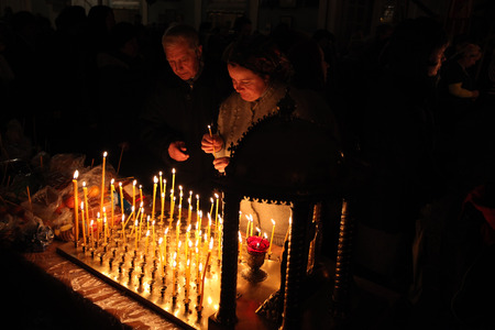 believers: PSKOV, RUSSIA - JANUARY 18, 2011: Orthodox believers light candles during the Epiphany evening service in the Church of Saint Alexander Nevsky in Pskov, Russia. Editorial