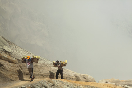KAWAH IJEN, INDONESIA - AUGUST 8, 2011: Miners carry baskets with sulphur in the fumes of toxic volcanic gas from the sulphur mines in the crater of the active volcano of Kawah Ijen, East Java, Indonesia.