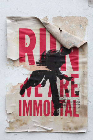 rebelling: PRAGUE, CZECH REPUBLIC - DECEMBER 20, 2012: Poster Run! We are Immortal! on a wall in Prague, Czech Republic.