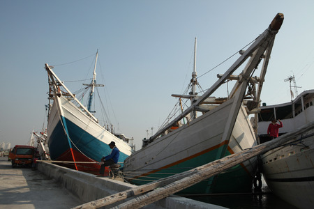 JAKARTA, INDONESIA - AUGUST 16, 2011: Wooden sailing ships called pinisi in the historical port of Sunda Kelapa in Jakarta, Central Java, Indonesia. Editöryel