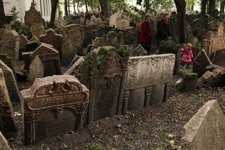 jewish quarter: PRAGUE, CZECH REPUBLIC - OCTOBER 15, 2012: People walk among abandoned tombstones at the Old Jewish Cemetery in Prague, Czech Republic. Editorial