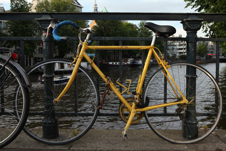 padlocked: AMSTERDAM, NETHERLANDS - AUGUST 9, 2012: Old yellow bicycle parked on the bridge over a gracht in Amsterdam, Netherlands.