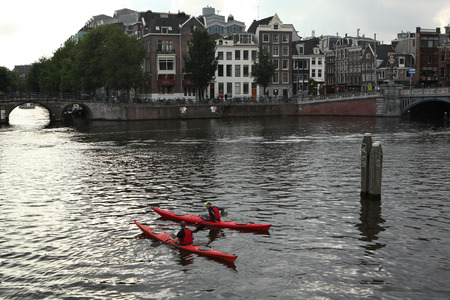amstel river: AMSTERDAM, NETHERLANDS - AUGUST 8, 2012: Two people on canoes training in the Amstel River near the Dutch National Opera in Amsterdam, Netherlands.