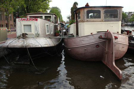 amstel river: AMSTERDAM, NETHERLANDS - AUGUST 8, 2012: Two houseboats moored on the Amstel River near the Dutch National Opera in Amsterdam, Netherlands. Editorial
