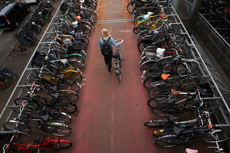 parking station: AMSTERDAM, NETHERLANDS - AUGUST 9, 2012: Woman pushes a bicycle on through the bicycle parking station next to the Central railway station in Amsterdam, Netherlands. Editorial