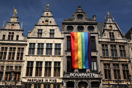 guildhall: ANTWERP, BELGIUM - AUGUST 12, 2012: Rainbow flag on the medieval guild houses at the Grote Markt in Antwerp, Belgium.