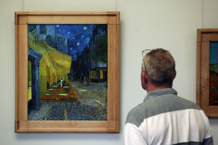OTTERLO, NETHERLANDS - AUGUST 8, 2012: Visitor looks at the painting Cafe Terrace at Night (1888) by Vincent van Gogh in the Kroller Muller Museum in Otterlo, Netherlands. 에디토리얼