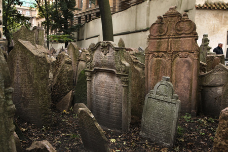 hebrew script: PRAGUE, CZECH REPUBLIC - OCTOBER 15, 2012: Visitor walks among abandoned tombstones at the Old Jewish Cemetery in Prague, Czech Republic. Editorial