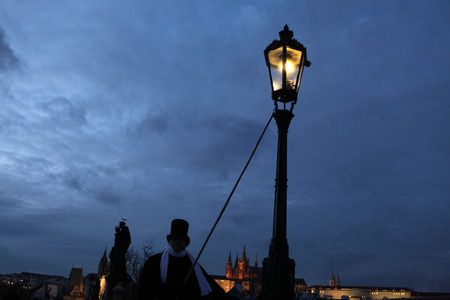 PRAGUE, CZECH REPUBLIC - DECEMBER 5, 2012: Lamplighter lights a street gas light manually during the Advent at the Charles Bridge in Prague, Czech Republic. Street gas lights in the historical centre of Prague are lighted manually during the Advent only a