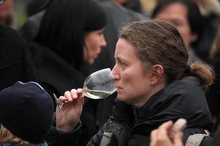 tastes: PRAGUE, CZECH REPUBLIC - NOVEMBER 11, 2012: Woman tastes young wine during the celebration of Saint Martin Day in Prague, Czech Republic.
