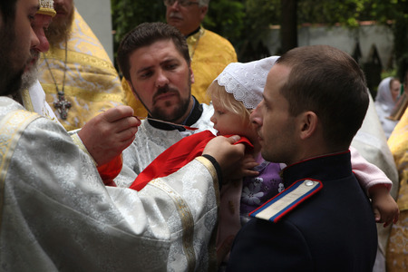 liturgical: PRAGUE, CZECH REPUBLIC - MAY 28, 2012: Young girl receives the Eucharist during an orthodox service in front of the Dormition Church at the Olsany Cemetery in Prague, Czech Republic.